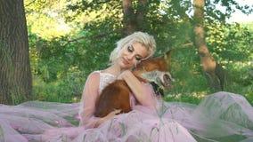 Piękna młoda kobieta z ślicznym lisem przy lasem zbiory wideo