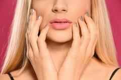 Piękna młoda kobieta z błyszczącym manicure'em na koloru tle Gwo?dzia po?ysku trendy fotografia royalty free