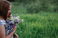 Piękna młoda kobieta z bouguet łąkowymi kwiatami cieszy się śródpolnych aromaty fotografia royalty free