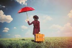 Piękna młoda kobieta z brown walizki i parasola pozycją Zdjęcia Stock