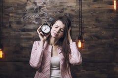 Piękna młoda kobieta z budzikiem w ręce t i kwaśnej twarzy Zdjęcia Stock