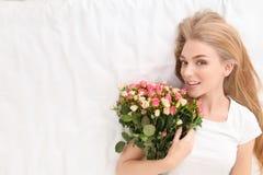Piękna młoda kobieta z bukietem róże Obrazy Royalty Free