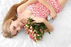 Piękna młoda kobieta z bukietem róże na łóżku Obraz Royalty Free