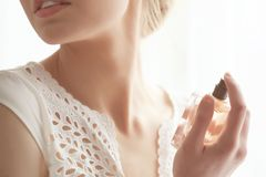 Piękna młoda kobieta z butelką pachnidło w domu, zdjęcia royalty free