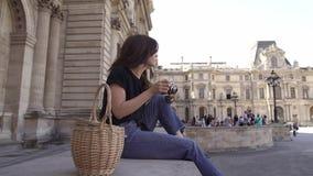 Piękna młoda kobieta z ciemnym włosy, będący ubranym cajgi i czarną koszulkę bierze obrazki miasto Lewica wyprostowywa? nieck? zbiory wideo