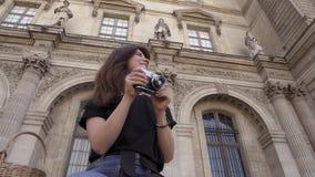 Piękna młoda kobieta z ciemnym włosy, będący ubranym cajgi i czarną koszulkę bierze obrazki miasto Rzeczywisty portret zbiory