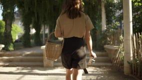 Piękna młoda kobieta z ciemnym włosy, będący ubranym czarnych skróty i beżową koszulkę chodzi w parku z koszem zbiory