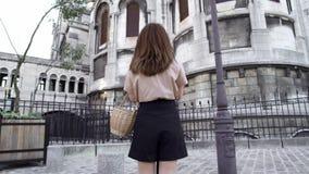 Piękna młoda kobieta z ciemnym włosy, ubierającym w czarnych skrótach i beżowej koszulce, bierze obrazki miasto Czas rzeczywisty zbiory wideo