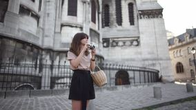 Piękna młoda kobieta z ciemnym włosy, ubierającym w czarnych skrótach i beżowej koszulce, bierze obrazki miasto Lewica zdjęcie wideo
