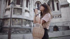 Piękna młoda kobieta z ciemnym włosy, ubierającym w czarnych skrótach i beżowej koszulce, bierze obrazki miasto wyprostowywa zbiory