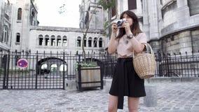 Piękna młoda kobieta z ciemnym włosy, ubierającym w czarnych skrótach i beżowej koszulce, bierze obrazki miasto wyprostowywa zbiory wideo