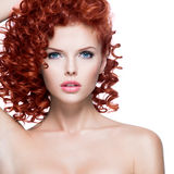 Piękna młoda kobieta z czerwonym kędzierzawym włosy Zdjęcia Stock