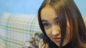 Piękna młoda kobieta z długie włosy obsiadaniem na leżance TV dopatrywaniu i zdjęcie wideo