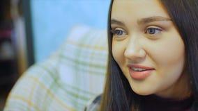 Piękna młoda kobieta z długie włosy obsiadaniem na leżance TV dopatrywaniu i zbiory wideo