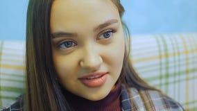 Piękna młoda kobieta z długie włosy obsiadaniem na leżance TV dopatrywaniu i zbiory