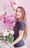 Piękna młoda kobieta z długim blondynka włosy, niebieskie oczy, kwiatonośna klatka, jest ubranym koszulkę Obrazy Stock