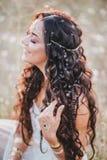 Piękna młoda kobieta z długim kędzierzawym włosy ubierał w boho stylu smokingowy pozować w polu z dandelions Fotografia Royalty Free