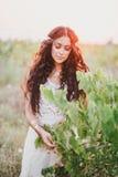 Piękna młoda kobieta z długim kędzierzawym włosy ubierał w boho stylu smokingowy pozować w polu z dandelions Zdjęcie Royalty Free