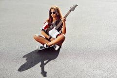 Piękna młoda kobieta z gitarą - plenerowy moda portret Obraz Stock