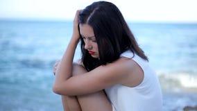 Piękna młoda kobieta z jaskrawymi czerwonymi wargami siedzi na seashore zbiory