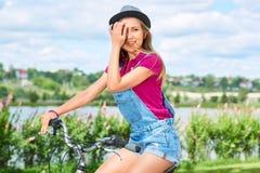 Piękna młoda kobieta z jej bicyklem przy parkiem obrazy stock
