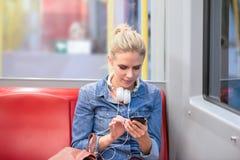 Piękna młoda kobieta z mądrze telefonem w metrze zdjęcie stock
