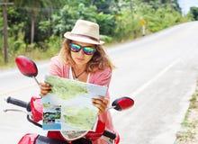 Piękna młoda kobieta z mapą w ręce i motocyklu na ro Obraz Royalty Free