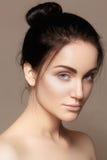 Piękna młoda kobieta z perfect czystą błyszczącą skórą, naturalny mody makeup Splendoru portret model z śliczną babeczki fryzurą obraz royalty free