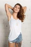 Piękna młoda kobieta z rękami za głową Biały ściana z cegieł, odizolowywający zdjęcie royalty free
