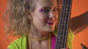 Piękna młoda kobieta z retro stylem uzupełnia, seductively liże gitary szyję, zdjęcie wideo