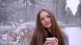 Piękna młoda kobieta z rozporządzalną filiżanką pije herbaty lub kawy outdoors w zima parku swobodny ruch zbiory wideo