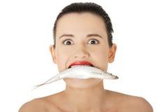 Piękna młoda kobieta z ryba w jej usta Obraz Stock