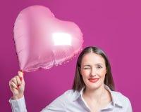 Piękna młoda kobieta z sercem kształtował balon na jaskrawym tle Walentynki ` s dnia pojęcie obrazy stock