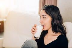 Piękna młoda kobieta z szkłem mleko w domu obrazy royalty free