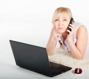 Piękna młoda kobieta z telefonem i laptopem kłama na ciepłej szkockiej kracie Fotografia Royalty Free