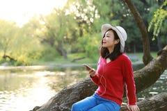 Piękna młoda kobieta z uśmiechem Słucha muzyka na telefonie komórkowym w parku i obsiadanie na drewnianym drzewie na rzece fotografia stock