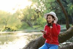 Piękna młoda kobieta z uśmiechem Słucha muzyka na telefonie komórkowym w parku i obsiadanie na drewnianym drzewie na rzece zdjęcia stock