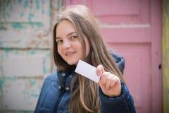 Piękna młoda kobieta z uśmiechem wystawia pustą wizytówkę zdjęcia royalty free