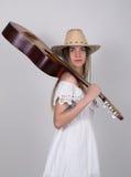 Piękna młoda leggy blond kraj dziewczyna w litl bielu kowbojskim kapeluszu z gitarą i sukni Obraz Royalty Free