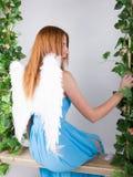 Piękna młoda leggy redhaired kobieta w długiej błękit sukni na huśtawce, drewniana huśtawka zawieszająca od linowego konopie, ark obrazy royalty free
