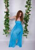 Piękna młoda leggy redhaired kobieta w długiej błękit sukni na huśtawce, drewniana huśtawka zawieszająca od linowego konopie, ark obraz royalty free