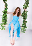 Piękna młoda leggy redhaired kobieta w długiej błękit sukni na huśtawce, drewniana huśtawka zawieszająca od linowego konopie, ark fotografia stock