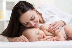 Piękna młoda mama patrzeje jej sypialnych małych ono uśmiecha się i dziecka Dziecka lying on the beach w łóżku w domu fotografia royalty free