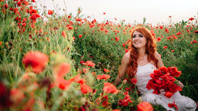 Piękna młoda miedzianowłosa kobieta trzyma bukiet maczki w maczka polu Zdjęcia Royalty Free