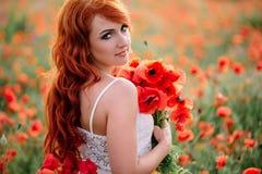 Piękna młoda miedzianowłosa kobieta trzyma bukiet maczki w maczka polu Fotografia Stock