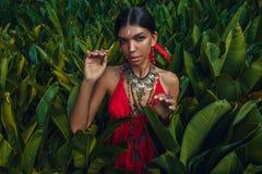 Piękna młoda modna kobieta z uzupełnia i eleganccy boho akcesoria pozuje na naturalnym tropikalnym tle zdjęcia royalty free