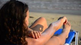 Piękna młoda nastoletnia stosuje słońce blokowa śmietanka zbiory