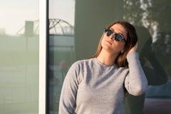 Piękna młoda nastoletnia uśmiechnięta dziewczyna pozuje przed szklanym okno Fotografia Royalty Free
