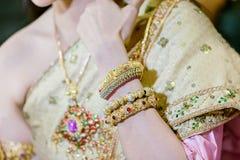 piękna młoda panna młoda kłaść ręki na podołek odzieży złocistych bransoletkach na jej ślubu diamentowym pierścionku i nadgarstku obraz stock