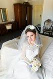Piękna młoda panna młoda z makeup, galanteryjna fryzura w biel sukni i przesłony obsiadanie na łóżku, zdjęcie royalty free